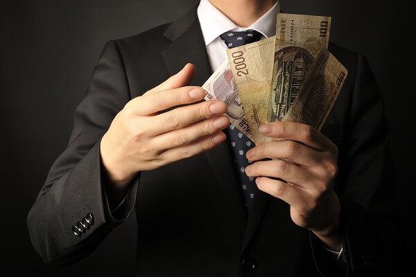 有料婚活サイトに支払うお金を数える男性